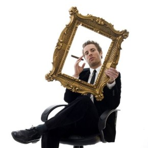 Business man smoking a cigar, looking through a golden frame